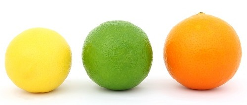 A lemon, lime, and orange lined up in a row against a white background.