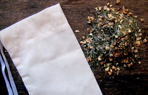 Image of a muslin back with dried herbs and flowers scattered next to it.