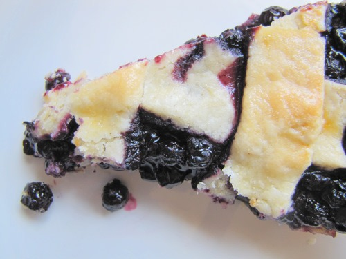 Bird's eye view of a slice of blueberry pie with a decorative lattice crust on a white background.