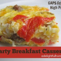 """Image of a serving of an egg casserole on a white plate. Text overlay says, """"Hearty Breakfast Casserole""""."""