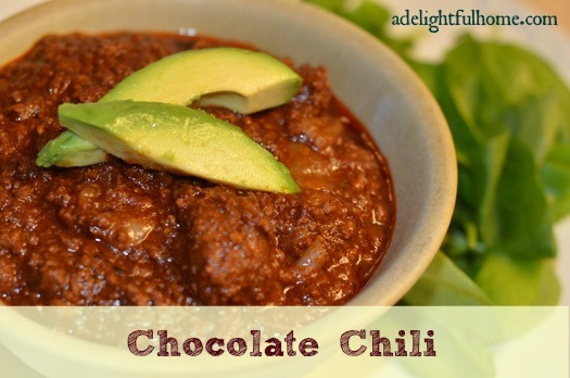 "Close up image of a bowl of chili garnished with avocado slices. Text overlay says, ""Chocolate Chili""."