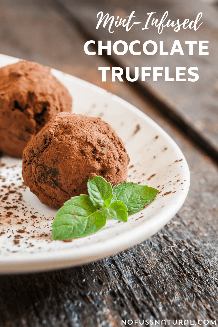 "Image of chocolate truffles on a white plate. Plate is dusted with cocoa powder, and garnished with fresh mint leaves. Text overlay says, ""Mint Infused Chocolate Truffles""."