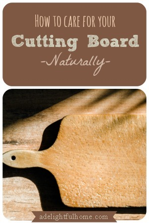 "Image of a wooden paddle style cutting board sitting on top of a butcher block. Text overlay says, ""How to Care for Your Cutting Board Naturally""."