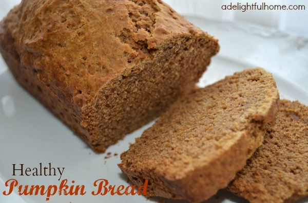 "Close up image of a loaf of sliced pumpkin bread served on a white platter. Text overlay says, ""Healthy Pumpkin Bread""."