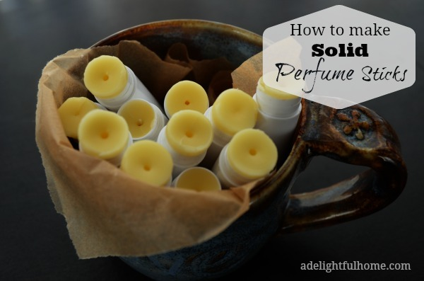 """Image of a pottery mug full of opened lip balm tubes to show contents. Text overlay says, """"How to Make Solid Perfume Sticks""""."""