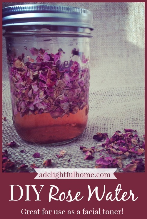 Mason jar filled with rose infused water. Dried rose petals are sprinkled in the foreground. Text overlay says, ""