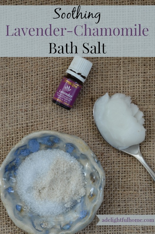 "Bird's eye view of a bowl full of bath salts. Lavender essential oil, and a spoonful of coconut oil sit to the side. Text overlay says, ""Soothing Lavender-Chamomile Bath Salt""."