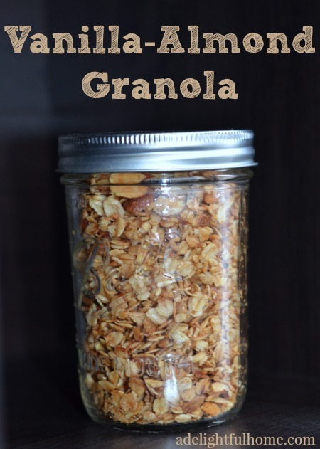 "Mason jar filled with homemade granola on a black background. Text overlay says, ""Vanilla-Almond Granola""."
