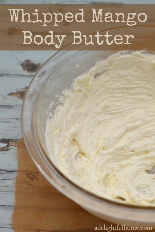 "A close up image of a bowl of whipped mango butter on a whitewashed table. Text overlay says, ""Whipped Mango Body Butter""."