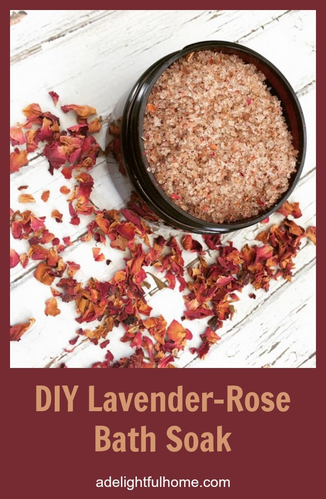 "Bird's eye view of an amber glass jar filled with rose colored bath salts. Dried rose petals are scattered around for decorative effect. Text overlay says, ""DIY Lavender-Rose Bath Soak""."