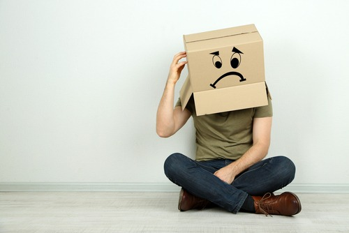 Image of a man sitting cross legged on the floor. A cardboard box with a frown face drawn on it sits on his head.