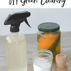 collection of DIY green cleaning supplies: glass spray bottle with homemade cleaner, fruit peel vinegar in jar, baking soda in jar, and wooden scrubbing brush