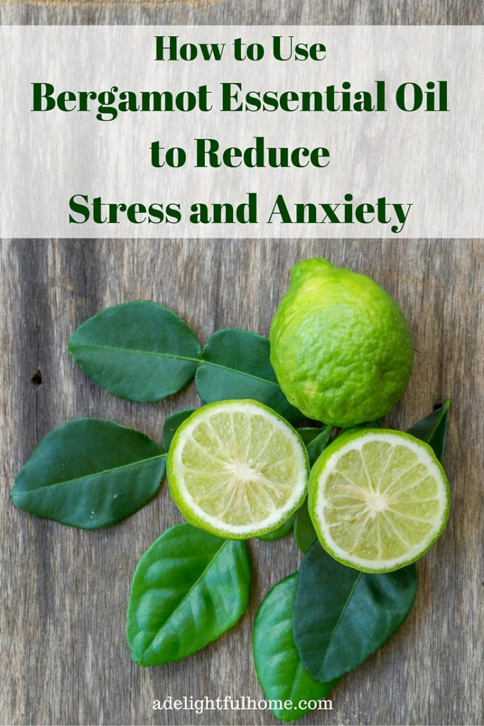 "A bird's eye view of fresh bergamot fruit and leaves on a natural wood surface. Text overlay says, ""How to Use Bergamot Essential Oil to Reduce Stress and Anxiety""."