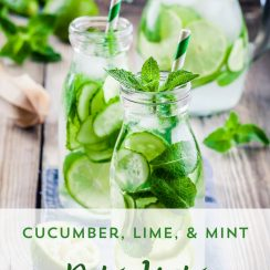 """Image of glass bottles filled with water infused with cucumber and lime slices, and garnished with mint leaves, and a decorative straw. A pitcher filled with more infused water sits in the background. Text overlay says, """"Cucumber, Lime, & Mint Detox Water""""."""