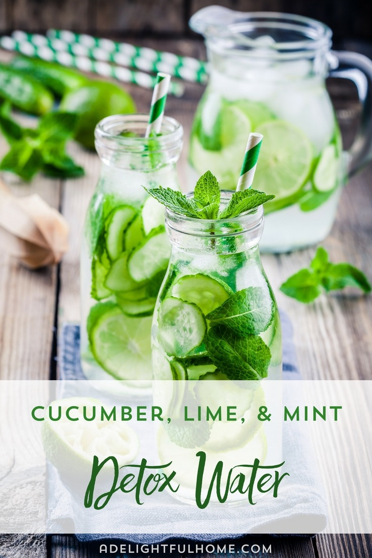 "Image of glass bottles filled with water infused with cucumber and lime slices, and garnished with mint leaves, and a decorative straw. A pitcher filled with more infused water sits in the background. Text overlay says, ""Cucumber, Lime, & Mint Detox Water""."
