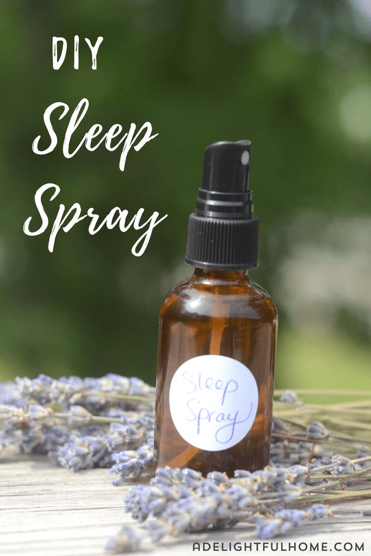 "Image of an amber spray bottle with a hand written label that says ""Sleep Spray"". Sprigs of lavender are arranged in the background. Text overlay says, ""DIY Sleep Spray""."