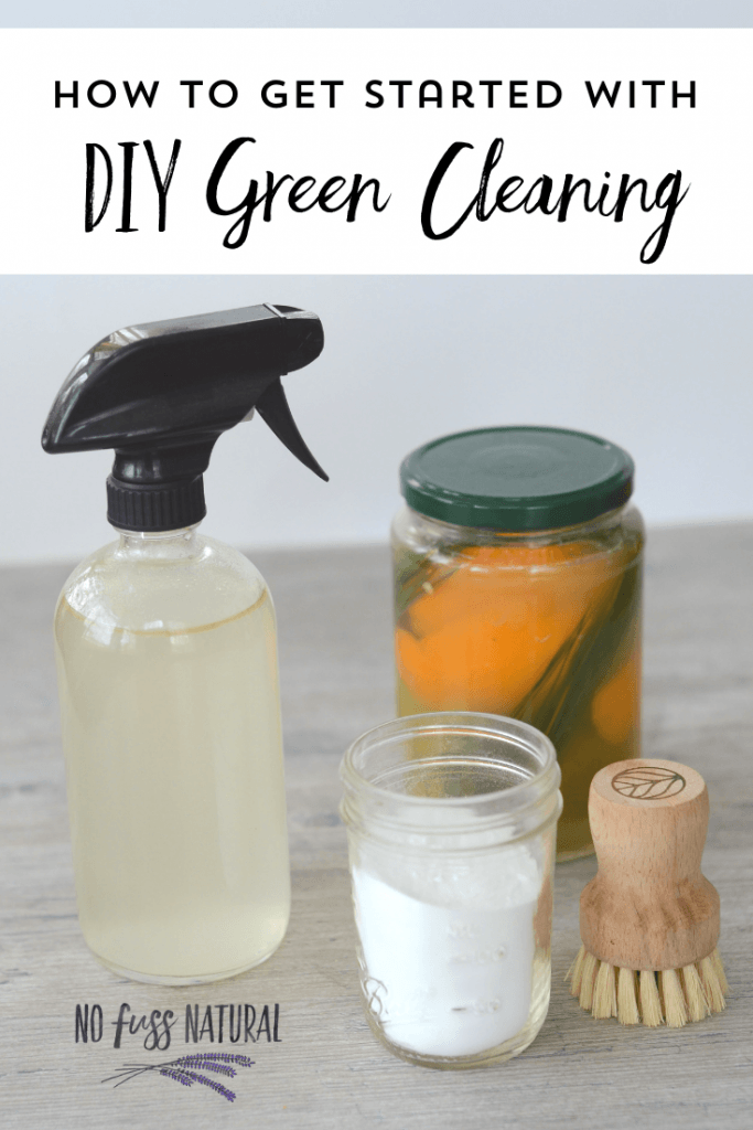 collection of green cleaning supplies: glass spray bottle with homemade cleaner, fruit peel vinegar in jar, baking soda in jar, and wooden scrubbing brush
