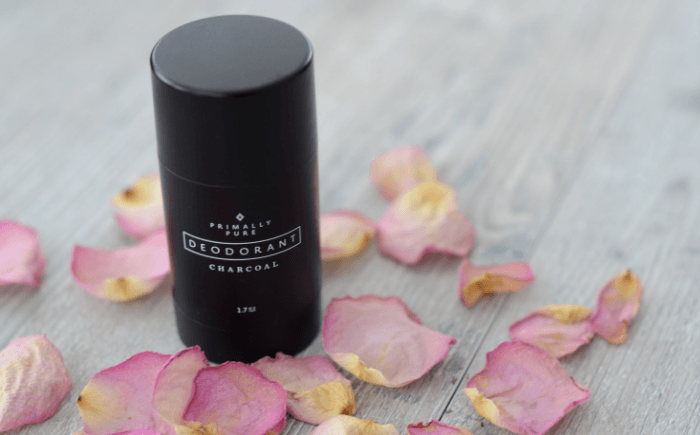 Container of natural charcoal deodorant with rose petals strew around it