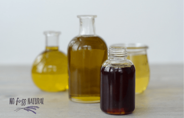 glass bottle with various carrier oils for homemade skincare