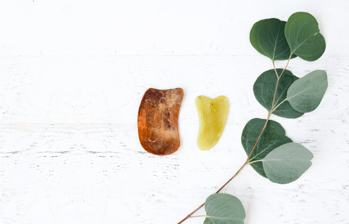 gua sha stones on table with eucalyptus leaf
