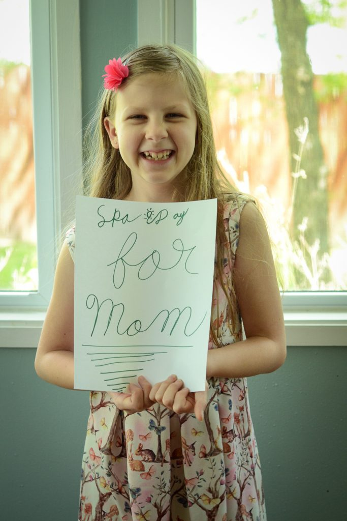 Kid with sign for Mothers day spa day